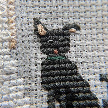 Funny black dog with cute ears cross-stitched