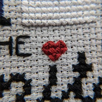 Tiny little red cross-stitched heart